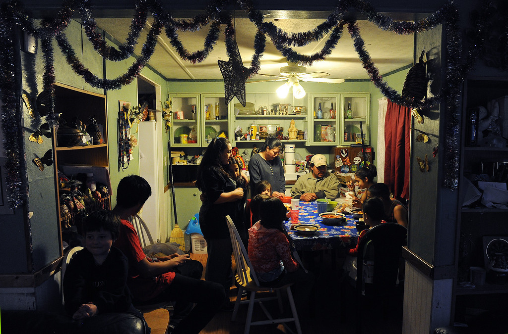 . GREELEY, CO - DECEMBER 16, 2013:  Norma Meza hugs her daughter Maria, 11 as Rosario Moreno, standing, and her husband Jose, seated, join some of the kids for dinner at the Meza\'s tiny home in Greeley, CO on December 16, 2013. The children seated at the table are from far right  clockwise:  Genoveva Meza, 14, Martin Meza jr., 17, Sergio Meza, 3, Janeth Moreno, 10, Edwin Moreno, 2, Yanna Moreno, 8.  At left are brothers Jared, 5, and Ivan, 18, Moreno. The Meza family, which consists of four children, Norma and her husband Martin have taken in the Moreno family after they lost everything in the September floods.  Rosario and her husband Jose have 5 children and are without a home at the moment.  Norma says she will help out her best friend for as long as she needs to.  The tiny house has 3 bedrooms and 2 small bathrooms and is home now to 14 people, 2 cats and 3 dogs.  (Photo By Helen H. Richardson/ The Denver Post)