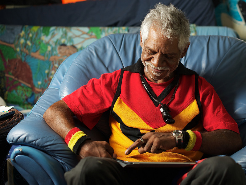 Aboriginal Man smiling while using a Tablet Computer