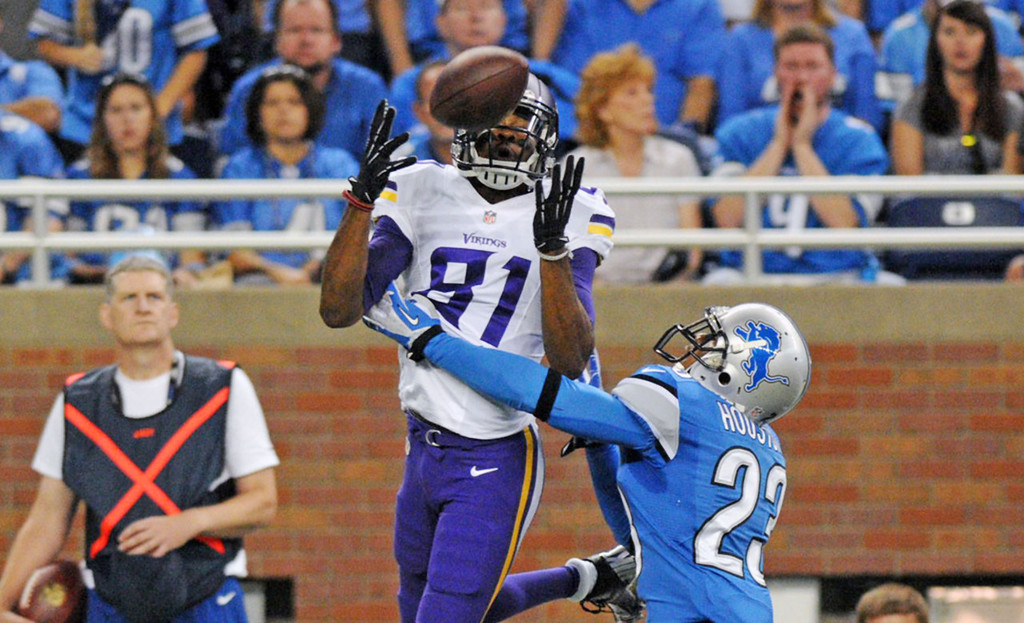 . Vikings wide receiver Jerome Simpson  makes a reception over Lions cornerback Chris Houston in the second quarter.  (Pioneer Press: Chris Polydoroff)