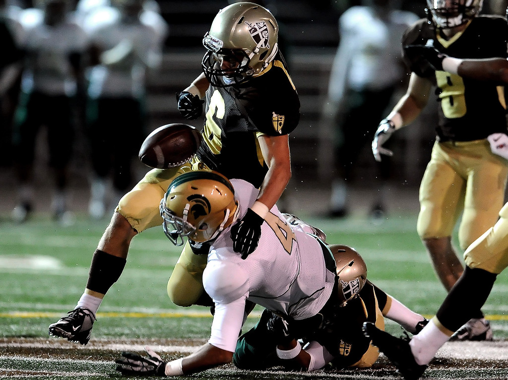 . Damien\'s Leroy Cloud (4) fumbles as St. Francis\' Joe Mudie (C) (6) knocks away the ball in the first half of a prep football game at St. Francis High School in La Canada, Calif., Friday, Sept. 27, 2013. St. Francis\' Mason Williams (not pictured) would recover the ball.   (Keith Birmingham Pasadena Star-News)