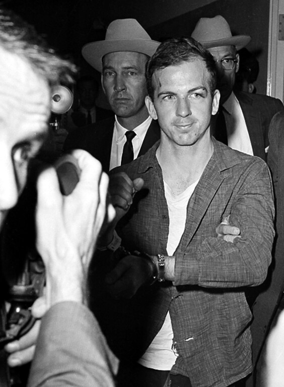 . Lee Harvey Oswald, suspected assassin of U.S. President John F. Kennedy, holds up his manacled hands at police headquarters in Dallas, Texas, where he is held for questioning, on Nov. 22, 1963. New testing on the type of ammunition used in the 1963 assassination of President John F. Kennedy raises questions about whether Lee Harvey Oswald acted alone, according to a study by researchers at Texas A&M University. (AP Photo/Ferd Kaufman)