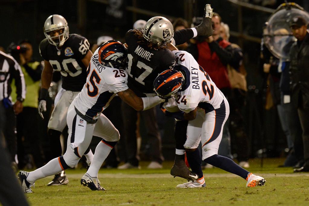 . Denver Broncos cornerback Chris Harris #25 and cornerback Champ Bailey #24 slam Oakland Raiders wide receiver Denarius Moore #17 at the O.co Coliseum, in Oakland , CA December 06, 2012.      Joe Amon, The Denver Post