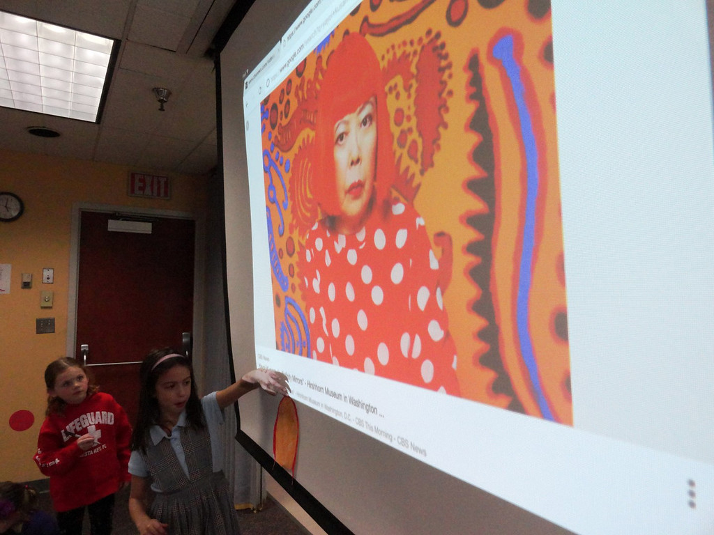 . Sarah Thacker places her portrait of Yayoi Kusama�s face alongside her picture. (Courtesy Mentor Public Library)