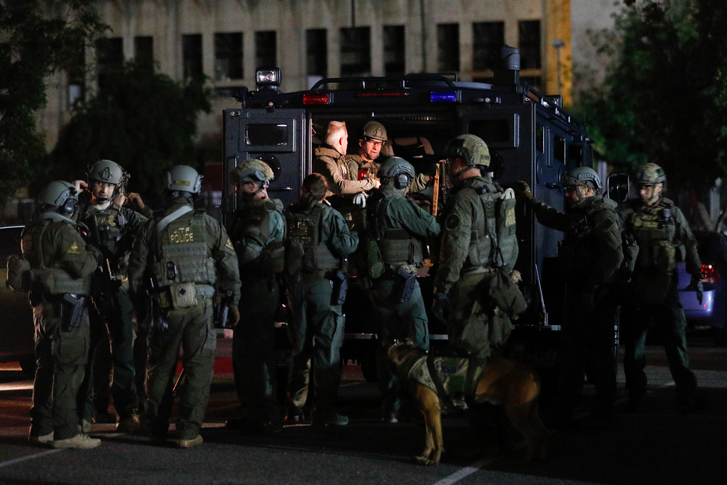 . ATF agents prepare for a raid in the parking lot of the Los Angeles Memorial Coliseum early Wednesday morning, May 17, 2017, in Los Angeles. Hundreds of federal and local law enforcement fanned out across Los Angeles, serving arrest and search warrants as part of a three-year investigation into the violent and brutal street gang MS-13. (AP Photo/Jae C. Hong)