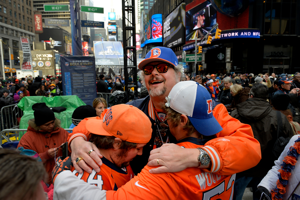 Description of . Broncos fans Justin Putnam, Malcolm O'Brien and Luke Hardy embrace while visiting Times Square in New York, NY January 31, 2014. The NFL has transformed 13 blocks of Broadway into Super Bowl Boulevard before Sundays Super Bowl between the Denver Broncos and Seattle Seahawks. O'Brien of Lakewood, CO, predicted a 77-3 Broncos victory.   (Photo By Craig F. Walker / The Denver Post)