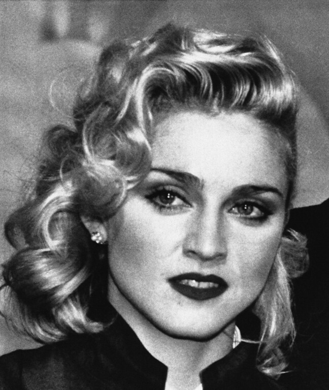 """. Rock star Madonna faces the press at London hotel in Thursday, March 7, 1986 in London, England during a news conference to promote the movie. \""""Shanghai Surprise\"""", in which she is starring. The film is being produced by Handmade Films, founded by former Beatle George Harrison. (AP Photo/Dave Caulkin)"""