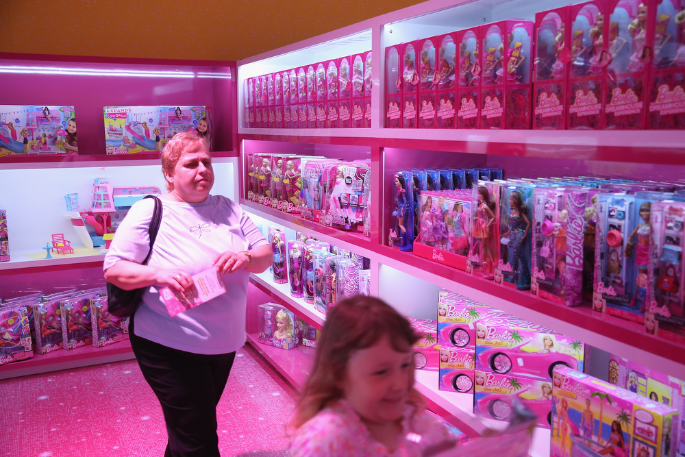 . Nele, 6, and her grandmother prepare to purchase a souvenir at the merchandising shop at the Barbie Dreamhouse Experience on May 16, 2013 in Berlin, Germany. The Barbie Dreamhouse is a life-sized house full of Barbie fashion, furniture and accessories and will be open to the public until August 25 before it moves on to other cities in Europe.  (Photo by Sean Gallup/Getty Images)