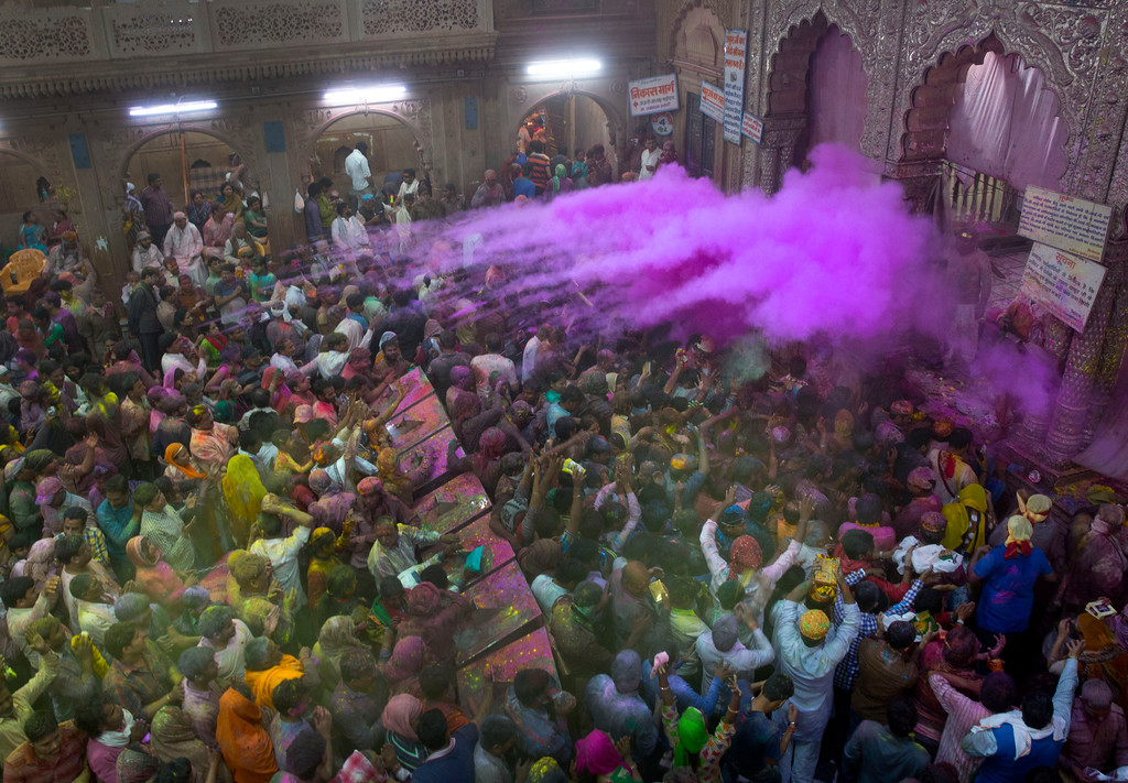 . Hindu priests throw color powders at the devotees inside Banke Bihari temple, dedicated to Lord Krishna, during Holi festival celebrations in Vrindavan, India, Wednesday, March 8, 2017. Holi, the festival of colors, celebrates the arrival of spring. (AP Photo/Manish Swarup)