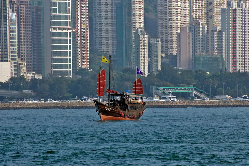 Solitary boat cruising at water in the Victoria Harbor in Hong Kong