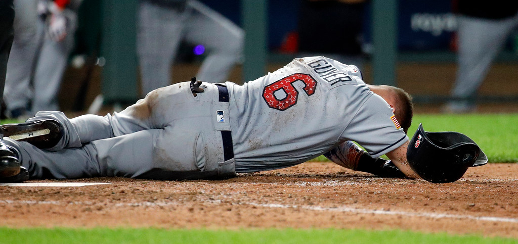 . Cleveland Indians\' Brandon Guyer lies on the ground after hitting a foul ball off his leg during the ninth inning of a baseball game against the Kansas City Royals on Tuesday, July 3, 2018, in Kansas City, Mo. (AP Photo/Charlie Riedel)