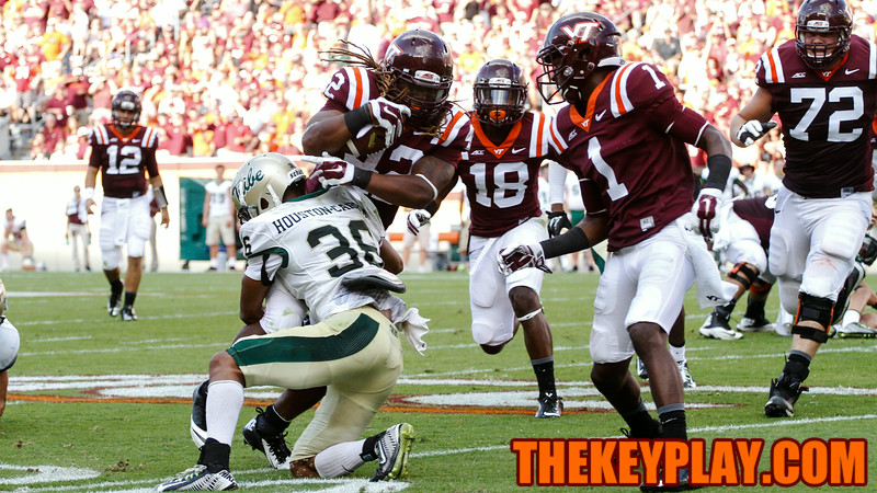 Marshawn Williams (42) breaks a tackle by William and Mary's DeAndre Houston-Carson (36)