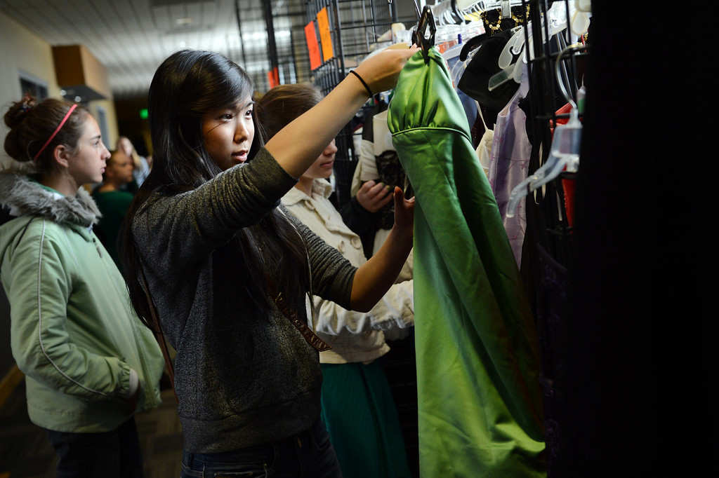 """. COMMERCE CITY, CO. - MARCH 16: Hitomi Okada, a senior at Green Mountain High School, looks for a dress at the Prom Dress Exchange Corp. event in Commerce City, CO March 16, 2013. With a valid student ID and a suggested $10 donation, teenage girls could chose from 1,356 donated dresses that lined a long hallway at Dick�s Sporting Goods Park. Okada said, I was shocked how generous this is... prom is really expensive.\"""" (Photo By Craig F. Walker/The Denver Post)"""