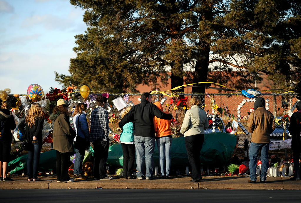 . Mourners visit the memorial for shooting victim Claire Davis along a fence outside Arapahoe High School in Centennial on Dec. 22, the day after her death. Photo by Jamie Cotten, Special to The Denver Post