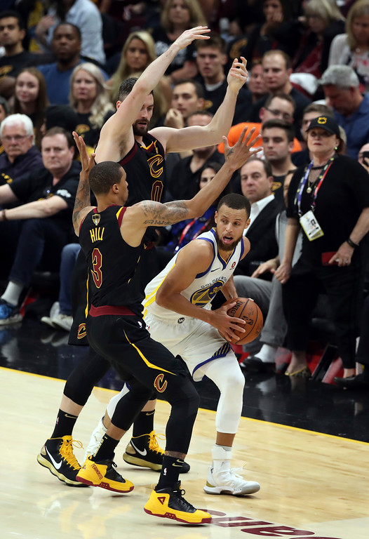 . Golden State Warriors\' Stephen Curry is defended by Cleveland Cavaliers\' George Hill (3) and Kevin Love during the first half of Game 4 of basketball\'s NBA Finals, Friday, June 8, 2018, in Cleveland. (AP Photo/Carlos Osorio)