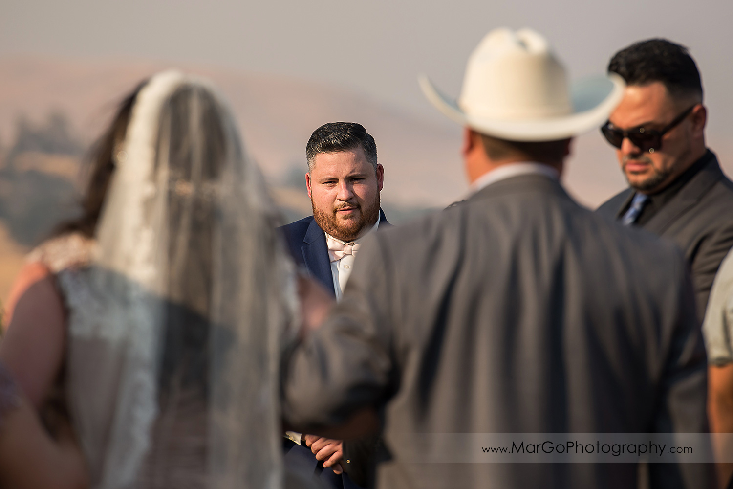 groom waiting form bride walking down the aisle during wedding ceremony at Taber Ranch Vineyards