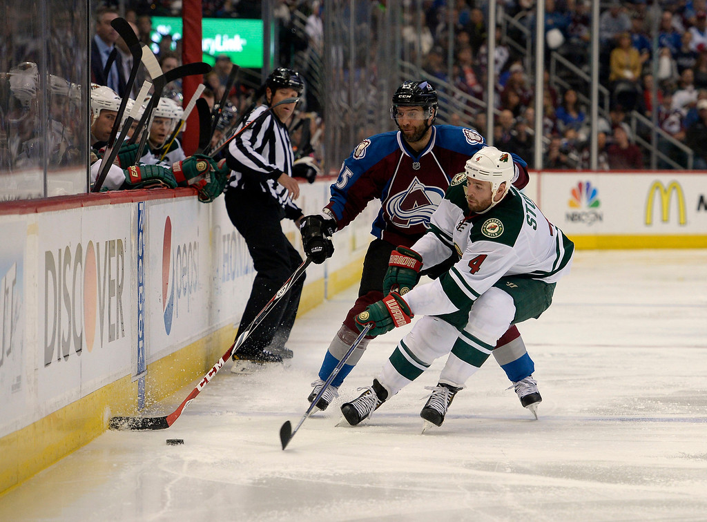 . Maxime Talbot (25) of the Colorado Avalanche fights for the puck along the boards with Clayton Stoner (4) of the Minnesota Wild during the third period of action. The Colorado Avalanche hosted the Minnesota Wild in the first round of the Stanley Cup Playoffs at the Pepsi Center in Denver, Colorado on Saturday, April 19, 2014. (Photo by John Leyba/The Denver Post)