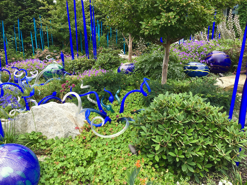 outdoor display of blue glass art mixed with greenery