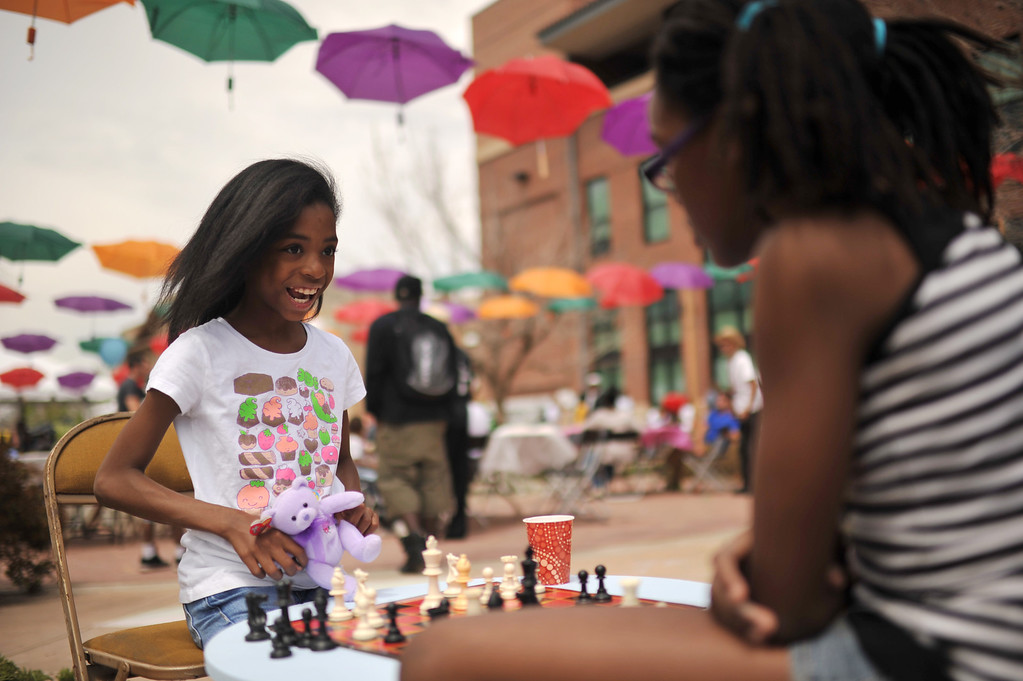 . DENVER, CO. - MAY 11 : Kaylyn Hollowell, 10, left, and her cousin Gabrielle Hollowell, 11, play chess at Five Points in Denver, Colorado. May 11, 2013. People are celebrating the Five Points Better Block Project at Sonny Lawson Park. The event was an opportunity for The Five Points Better Block Project to demonstrate potential improvements for the neighborhood and provide tips to promote a stronger community. (Photo By Hyoung Chang/The Denver Post)