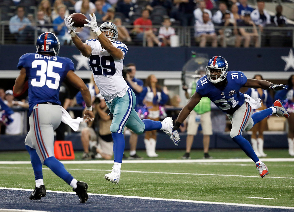 . New York Giants\' Quintin Demps (35) and Zack Bowman (31) defend as Dallas Cowboys tight end Gavin Escobar (89) comes down with a reception for a touchdown during the second half of an NFL football game Sunday, Oct. 19, 2014, in Arlington, Texas. (AP Photo/Brandon Wade)