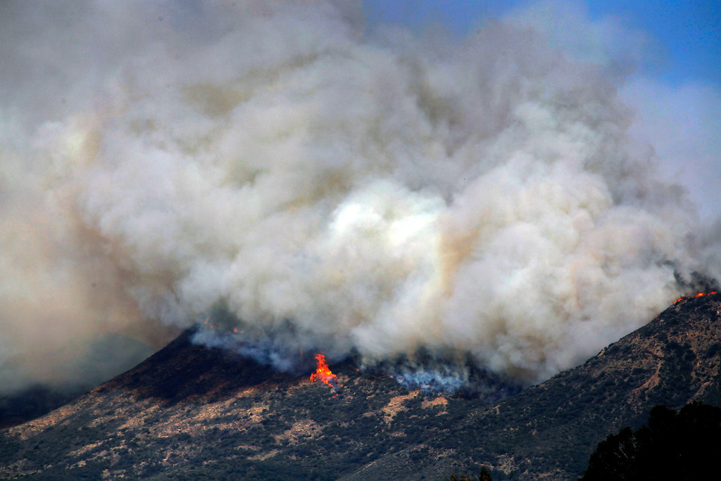 . Smoke and fire billows over a hill near Thousand Oaks, Calif. on Thursday, May 2, 2013.  (AP Photo/Nick Ut)
