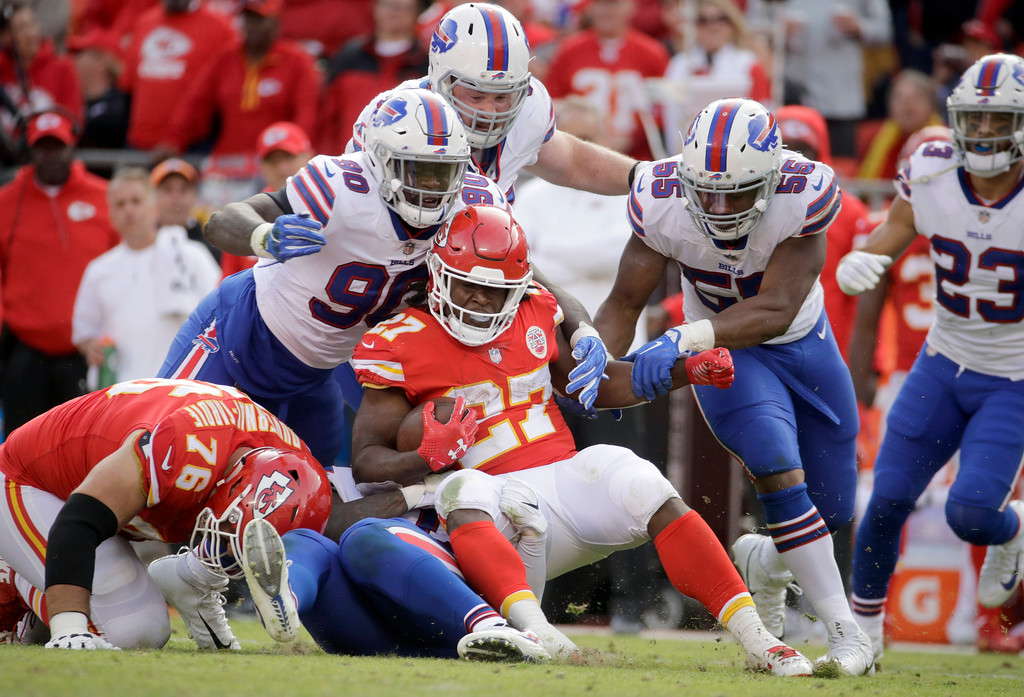 . Kansas City Chiefs running back Kareem Hunt (27) is tackled by Buffalo Bills defensive end Shaq Lawson (90), defensive tackle Kyle Williams, top, and defensive end Jerry Hughes (55) during the second half of an NFL football game in Kansas City, Mo., Sunday, Nov. 26, 2017. (AP Photo/Charlie Riedel)