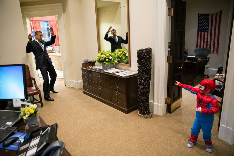 ". Oct. 26, 2012 ""The President to be caught in Spider-Man\'s web as he greets the Nicholas Tamarin, 3, just outside the Oval Office. Spider-Man had been trick-or-treating for an early Halloween with his father, White House aide Nate Tamarin in the Eisenhower Executive Office Building. I can never commit to calling any picture my favorite, but the President told me that this was HIS favorite picture of the year when he saw it hanging in the West Wing a couple of weeks later.\"" (Official White House Photo by Pete Souza)"