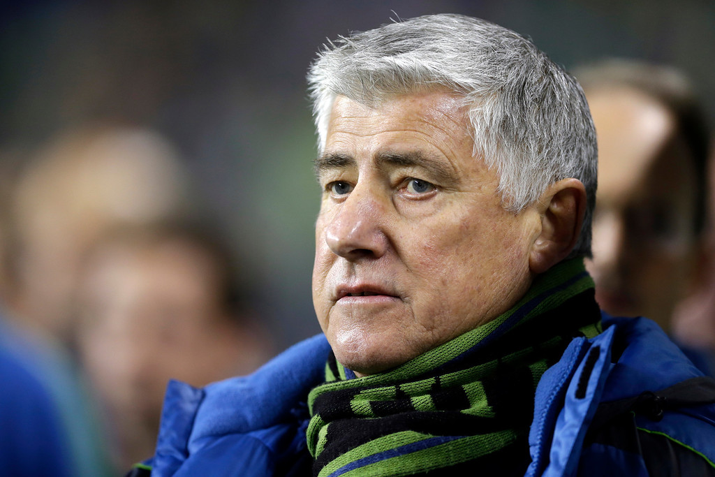 . Seattle Sounders head coach Sigi Schmid stands with his team during the national anthem before the first half of a knockout-round match against the Colorado Rapids in the MLS Cup soccer playoffs Wednesday, Oct. 30, 2013, in Seattle. (AP Photo/Ted S. Warren)