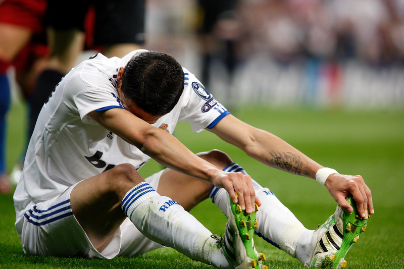 Di Maria sitting on the ground and stretching after a foul, UEFA Champions League Semifinals game between Real Madrid and FC Barcelona, Bernabeu Stadiumn, Madrid, Spain