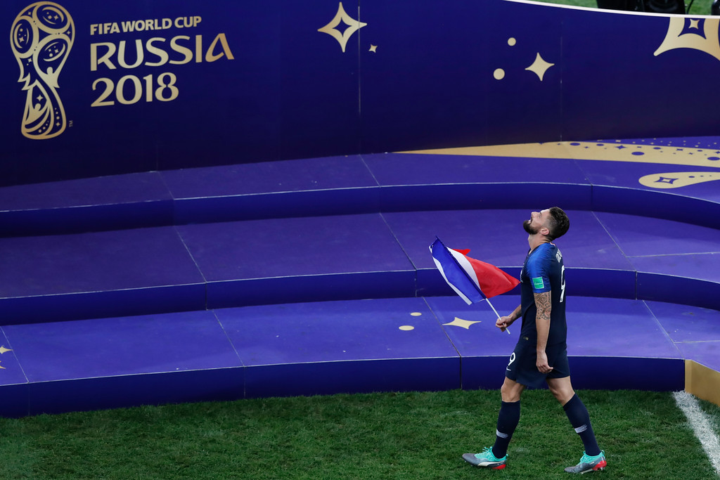 . France\'s Olivier Giroud holds a French flag as he celebrates at the end of the final match between France and Croatia at the 2018 soccer World Cup in the Luzhniki Stadium in Moscow, Russia, Sunday, July 15, 2018. (AP Photo/Rebecca Blackwell)