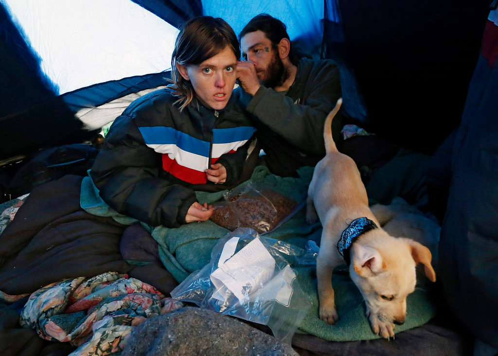 . Sarah Davis, left, and John Davis, right, try to stay warm in their in their tent at a homeless encampment in Oklahoma City, Friday, Dec. 6, 2013. Despite the recent winter storm, they do not want to leave their tent to go to a shelter. Oklahoma Gov. Mary Fallin declared a state of emergency for all 77 counties Thursday as the first storm moved across the state. (AP Photo/Sue Ogrocki)