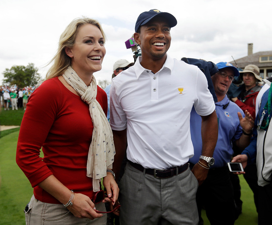 . United States team player Tiger Woods, right, smiles with girlfriend Lindsey Vonn after U.S. won the Presidents Cup golf tournament at Muirfield Village Golf Club Sunday, Oct. 6, 2013, in Dublin, Ohio. (AP Photo/Darron Cummings)