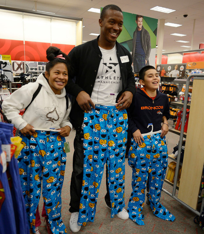 . Broncos wide receivers Demaryius Thomas poses with cookie monster pajamas with Amanda (L) and Guadalupe Jose as they shop for their family. Broncos wide receivers Demaryius Thomas and Eric Decker, along with other teammates, reached out to help children in their community by hosting a holiday shopping trip at Super Target Tuesday, December 11, 2012 in Lone Tree. 25 children, ranging in age from 8 to 14, are being rewarded for their outstanding participation in their after-school program with a trip to buy holiday presents. John Leyba, The Denver Post