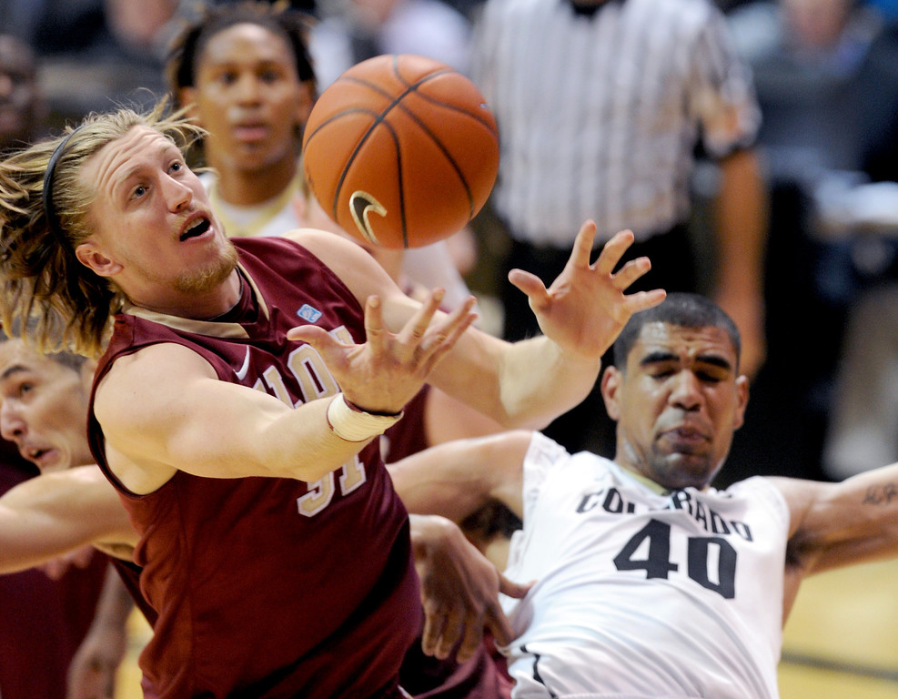. Luca Troutman of Elon and Josh Scott of CU  battle under the boards during the second half of the December 13, 2013 game in Boulder. (Cliff Grassmick/Boulder Daily Camera)
