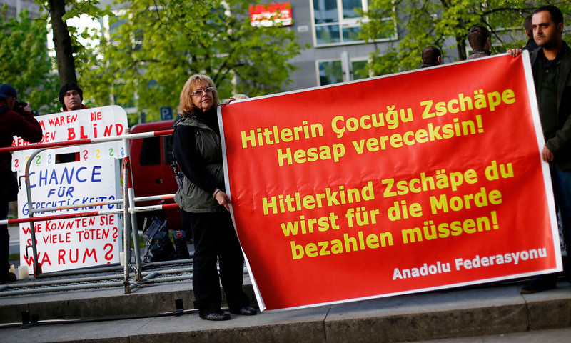 ". Protesters hold placards in front of a courthouse, where the trial against Beate Zschaepe, a member of the neo-Nazi group National Socialist Underground (NSU), began in Munich on May 6, 2013. The surviving member of NSU blamed for a series of racist murders that scandalized Germany and shamed its authorities goes on trial on Monday in one of the most anticipated court cases in recent German history. The trial in Munich will focus on 38-year-old Zschaepe, who is charged with complicity in the murder of eight Turks, a Greek and a policewoman between 2000-2007, as well as two bombings in immigrant areas of Cologne, and 15 bank robberies. Four others charged with assisting the NSU will sit with Zschaepe on the bench. The placards read (L, from top to bottom), ""Why have the authorities been blind, a chance for justice and how could they kill so many\"" and (R) \""Hitler\'s child Zschaepe you will pay for your murders\"". REUTERS/Kai Pfaffenbach"
