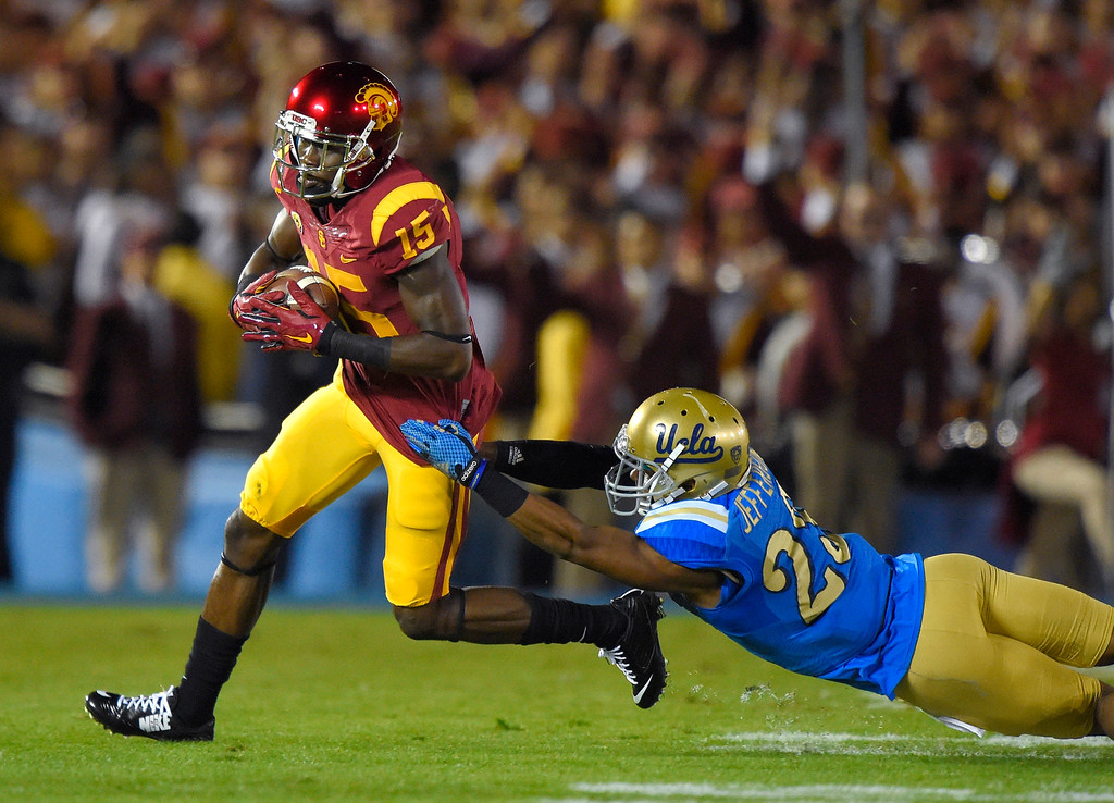 . Southern California wide receiver Nelson Agholor, left, escapes a tackle by UCLA defensive back Anthony Jefferson during the first half of an NCAA college football game, Saturday, Nov. 22, 2014, in Pasadena, Calif. (AP Photo/Mark J. Terrill)