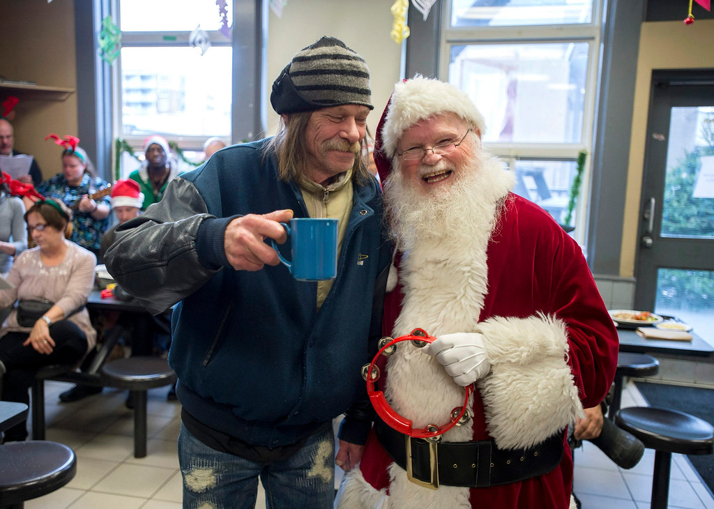 . Gilles Villeneuve, left, greets Raymond Tremblay, dressed as Santa Claus, at the Shepherds of Good Hope Christmas luncheon in Ottawa, Ontario, Thursday, Dec. 25, 2014. (AP Photo/The Canadian Press, Justin Tang)