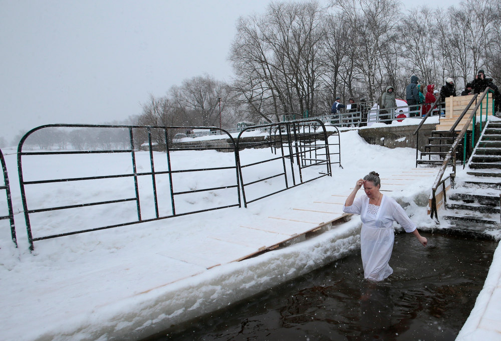 Description of . A woman crosses herself while bathing  in the ice cold water of the Moskva River, in Moscow, Russia, Friday, Jan. 18, 2013. Thousands of Russian Orthodox Church followers on Friday and Saturday will plunge into icy rivers and ponds across the country to mark the upcoming Epiphany, cleansing themselves with water deemed holy for the day. Water that is blessed by a cleric on Epiphany is considered holy and pure until next year's celebration, and is believed to have special powers of protection and healing. The Russian Orthodox Church follows the old Julian calendar, according to which Epiphany falls on Jan. 19. Moscow temperatures on Friday dropped to -15 Celcius (5 Fahrenheit). (AP Photo/Mikhail Metzel)