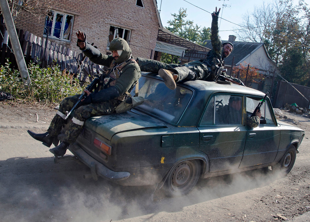 . Pro-Russian rebels ride atop a car to their positions not far from the Donetsk Sergey Prokofiev International Airport in the city of Donetsk, eastern Ukraine, Tuesday, Oct. 14, 2014. (AP Photo/Dmitry Lovetsky, File)