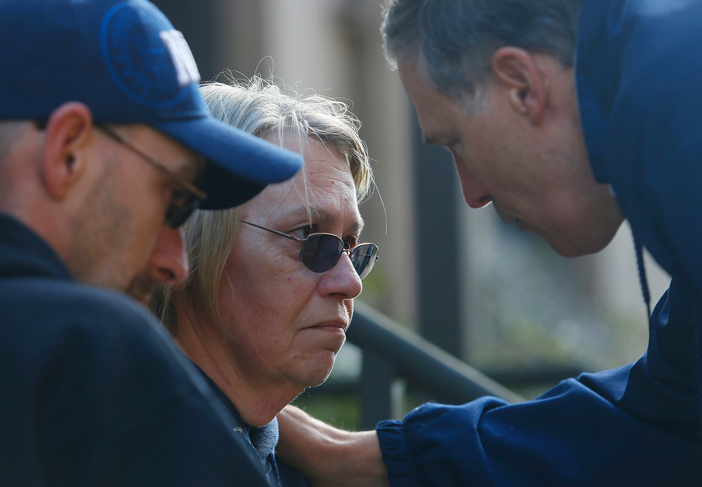 . Governor Jay Inslee, right, comforts Barbara Welsh, center, in downtown Arlington, Wash.,  Sunday, March 23, 2014. Barbara has not heard from her husband, who was in the slide area helping install a water heater on Saturday when the slide occurred.  (AP Photo /The Herald, Mark Mulligan)
