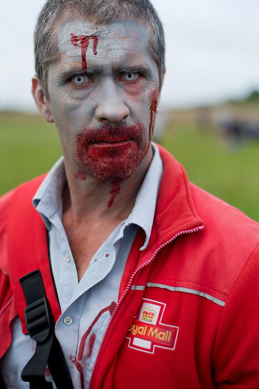""". A volunteer zombie Royal Mail postman prepares to take part in one of Britain\'s biggest horror events, the \""""Zombie Evacuation Race\"""" at Carver Barracks near Saffron Walden, England, on October 5, 2013. The race sees thousands of participants attempt to complete a gruelling 5 kilometre cross-country run, while evading \""""zombies\"""", intent on snatching the three life-line strips hanging from every runner\'s waist.  Those who manage to get through with any strips remaining are named as survivors while those without take home an \""""infected\"""" badge.  LEON NEAL/AFP/Getty Images"""