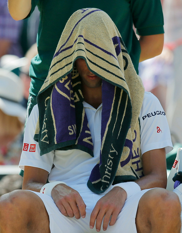 . Novak Djokovic of Serbia covers his head under a towel to cool down during a games break as he plays against Grigor Dimitrov of Bulgaria  during their men�s singles semifinal match at the All England Lawn Tennis Championships in Wimbledon, London, Friday, July 4, 2014. (AP Photo/Pavel Golovkin)