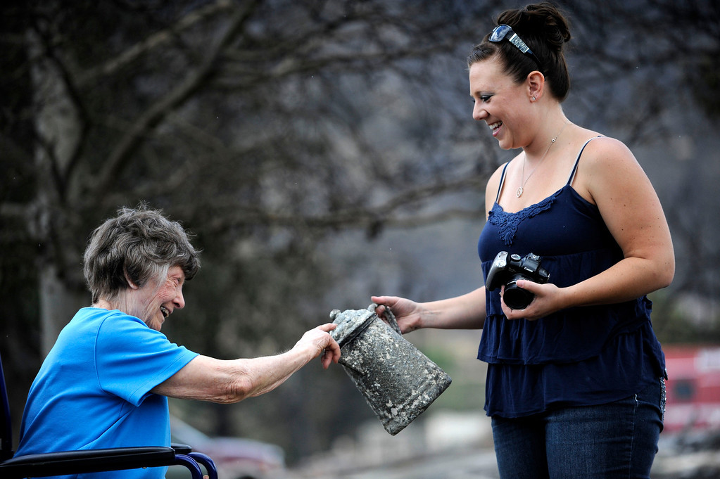 . Lauretta Anzalone, 80, smiles and shares a story with Cortney Lee, her great niece, as she shows her a kettle she found in the ashes of Anzalone\'s home that burnt to the ground in the Mountain Shadow subdivision of Colorado Springs where many homes were destroyed by the Waldo Canyon Fire. Heather Rousseau, The Denver Post