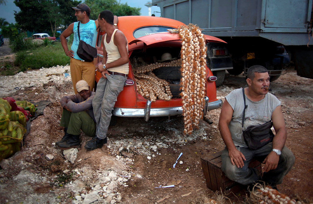 . In this Sept. 30, 2013 photo, farmers wait for customers next to their 1950s Chevrolet loaded with garlic for sale at the 114th Street Market on the outskirts of Havana, Cuba. The marketís bustle is a result of economic reforms begun in 2010 by President Raul Castro, which includes relaxing rules on private farming. (AP Photo/Ramon Espinosa)