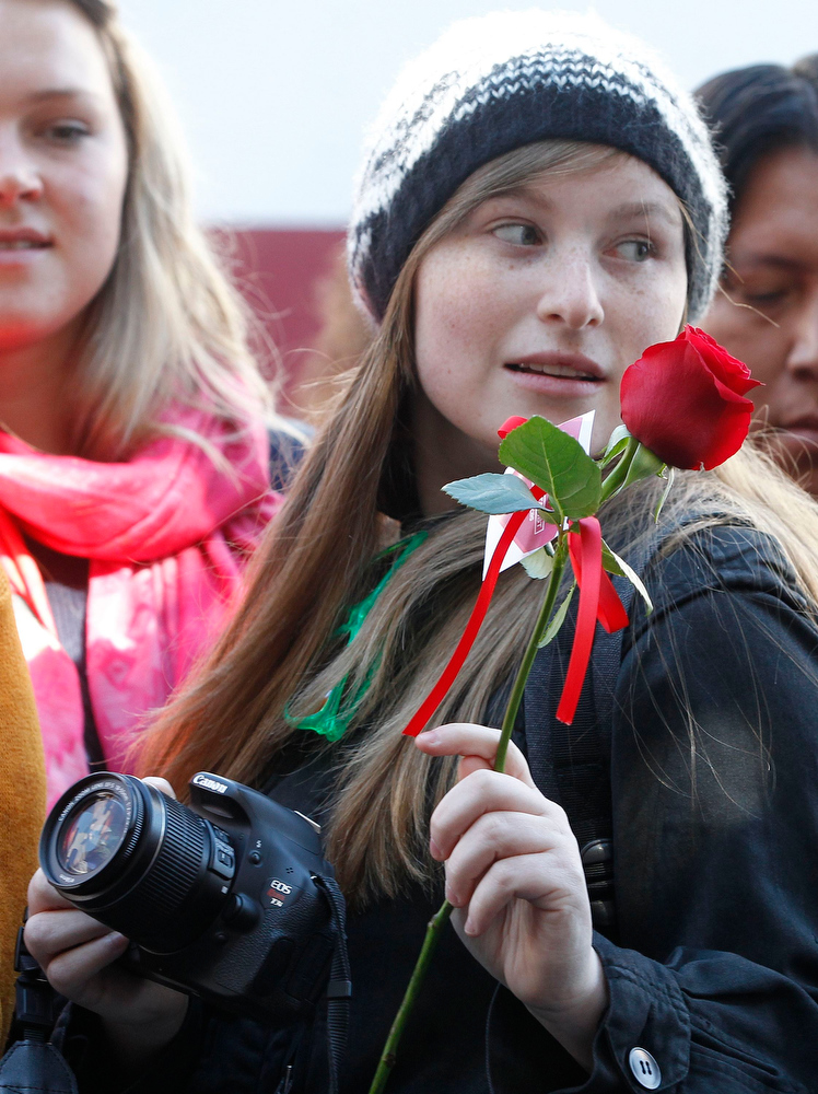Description of . Fan Abbie Bender from Denver, Colorado holds a rose handed out to fans on Valentine's Day during ceremonies honoring Australian actor Simon Baker with a star on the Hollywood Walk of Fame in Hollywood February 14, 2013.  REUTERS/Fred Prouser