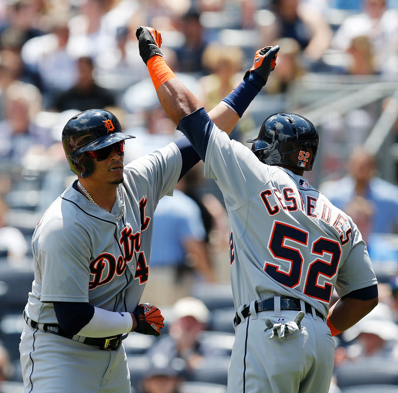 . Detroit Tigers on deck-batter Yoenis Cespedes (52) greets Tigers designated hitter Victor Martinez (41) after Martinez hit a first-inning, two-run home run in a baseball game against the New York Yankees at Yankee Stadium in New York, Sunday, June 21, 2015.  (AP Photo/Kathy Willens)