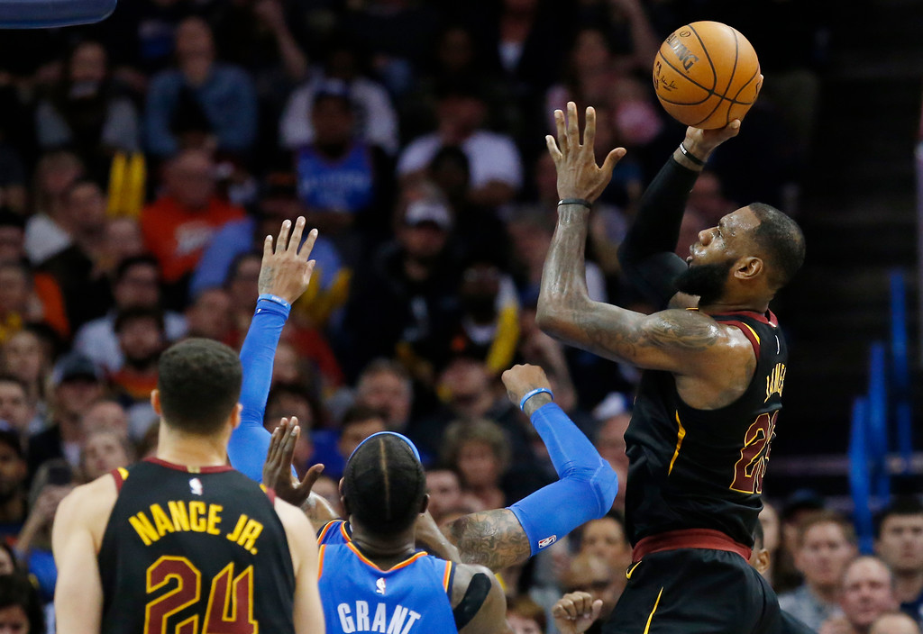 . Cleveland Cavaliers forward LeBron James, right, shoots against the Oklahoma City Thunder in the second half of an NBA basketball game in Oklahoma City, Tuesday, Feb. 13, 2018. (AP Photo/Sue Ogrocki)