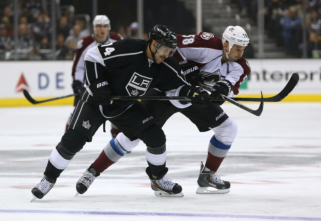 . LOS ANGELES, CA - NOVEMBER 23:  Dwight King #74 of the Los Angeles Kings and Patrick Bordeleau #58 of the Colorado Avalanche vie for position during a neutral zone face-off in the first period of the NHL game at Staples Center on November 23, 2013 in Los Angeles, California.  (Photo by Victor Decolongon/Getty Images)