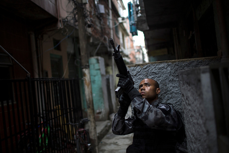 """. A military police officer takes position during an operation in the Mare slum complex, ahead of its \""""pacification,\"""" in Rio de Janeiro, Brazil, Tuesday, March 25, 2014. (AP Photo/Felipe Dana)"""