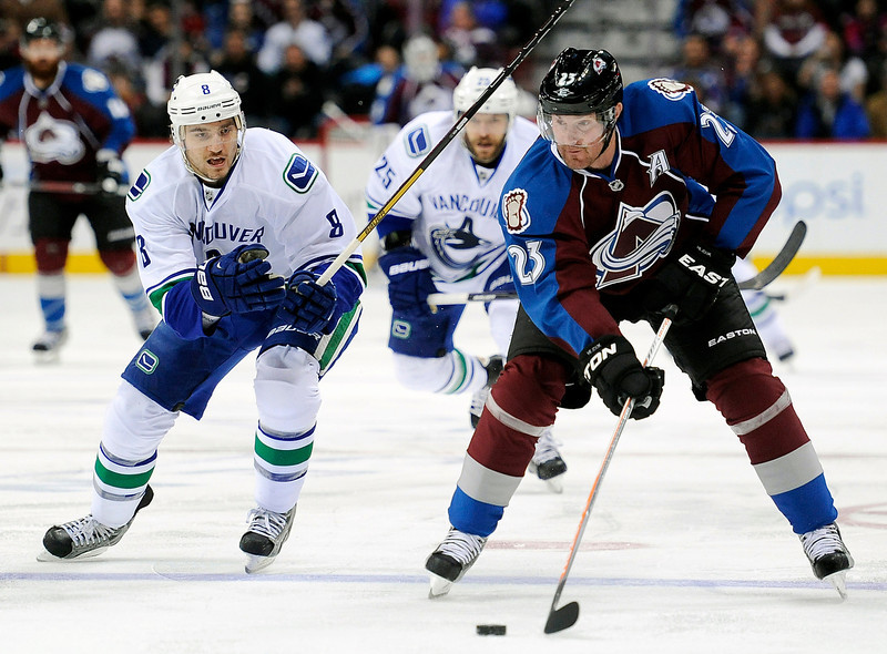 . Vancouver Canucks defenseman Chris Tanev, left, defends Colorado Avalanche right wing Milan Hejduk, right, of Czech Republic, in an NHL hockey game in Denver. Hejduk, 38, is retiring from the NHL after 14 seasons, all with the Avalanche. (AP Photo/Chris Schneider, File)