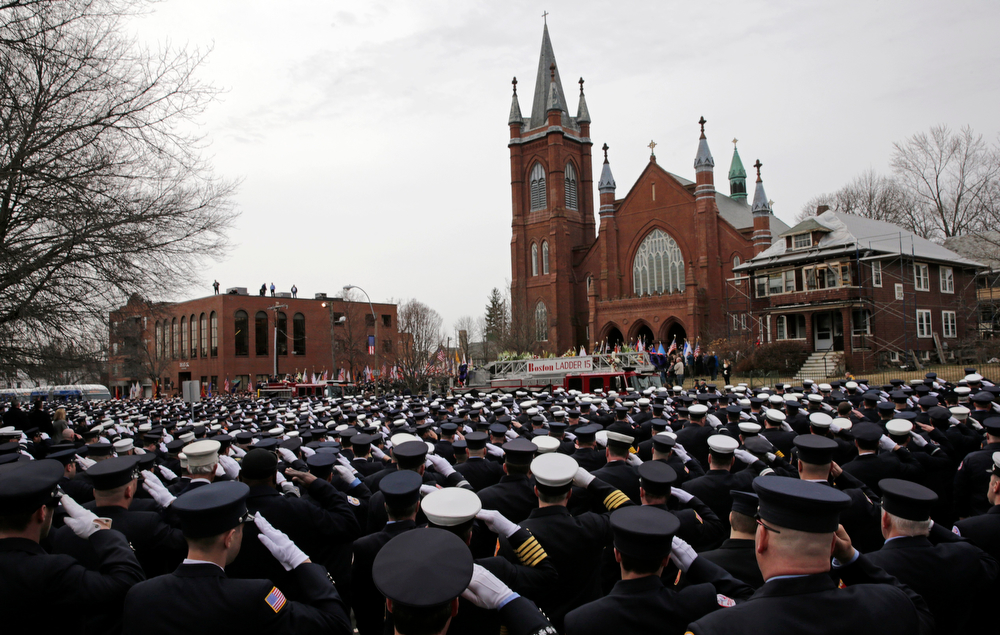 Description of . Firefighters salute as the casket of Boston Fire Lt. Edward Walsh is lowered from Engine 33 as it arrives outside the Church of Saint Patrick in Watertown, Mass., Wednesday, April 2, 2014. Walsh and Boston Firefighter Michael Kennedy died after being trapped while battling a fire in Boston. (AP Photo/Charles Krupa)